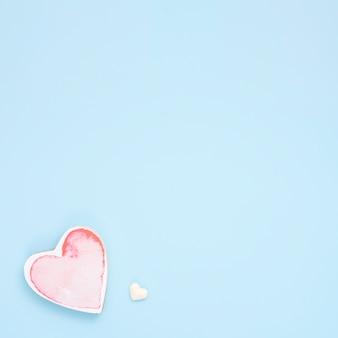 Pequeno coração vermelho na mesa azul