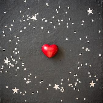 Pequeno coração vermelho no fundo preto com estrelas de prata do dia dos namorados e o conceito de natal