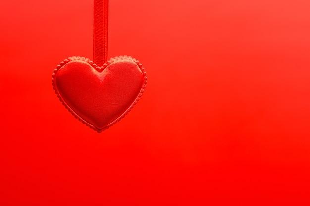Pequeno coração vermelho pendurado na fita