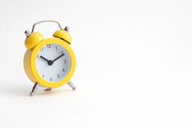 Pequeno despertador amarelo com sino isolado no fundo branco.