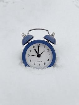 Pequeno despertador azul parado na neve