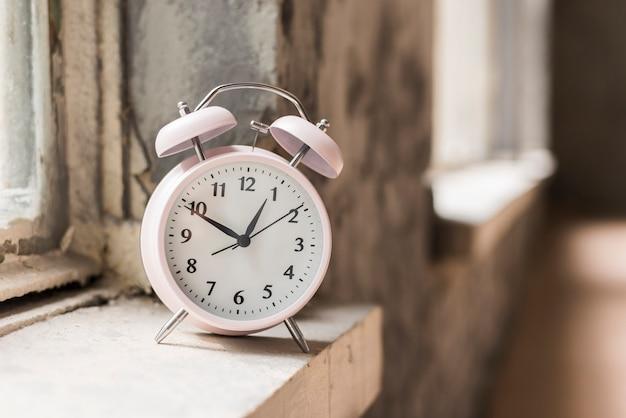 Pequeno despertador no peitoril de madeira perto da janela