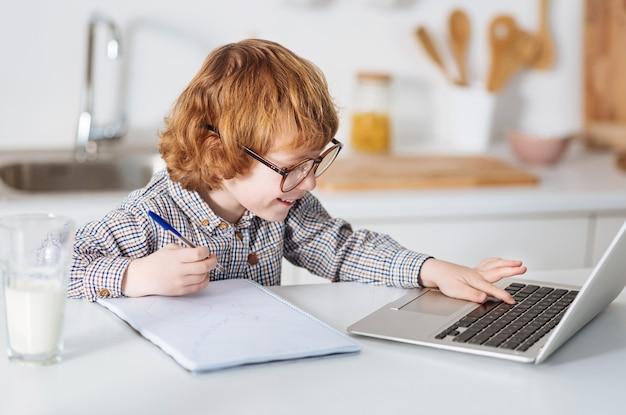 Pequeno einstein. jovem estudante produtivo, escrevendo algumas dicas enquanto pesquisa na internet e segura uma caneta na mão