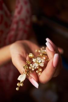 Pequeno em forma de gancho de cabelo dourado de flores na mão de uma menina
