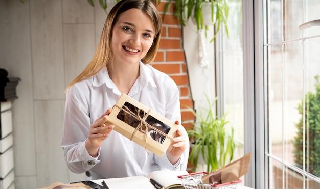 Pequeno empresário. mulher de negócios apresenta os produtos da loja online em uma caixa para a câmera. entrega e venda de alimentos online. o vendedor anuncia alimentos saudáveis. pequenos negócios
