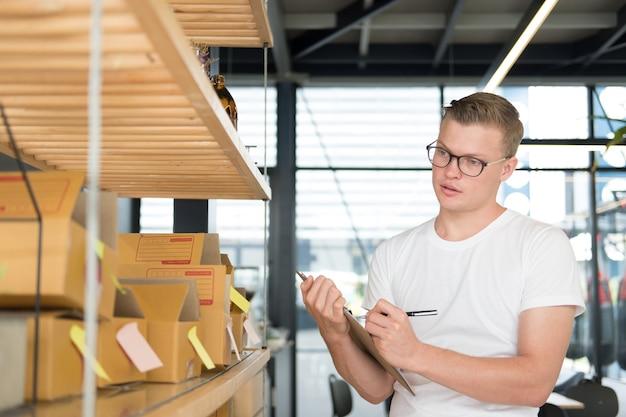 Pequeno empresário trabalhando no local de trabalho. ordem de verificação de vendedor de homem freelance para entrega