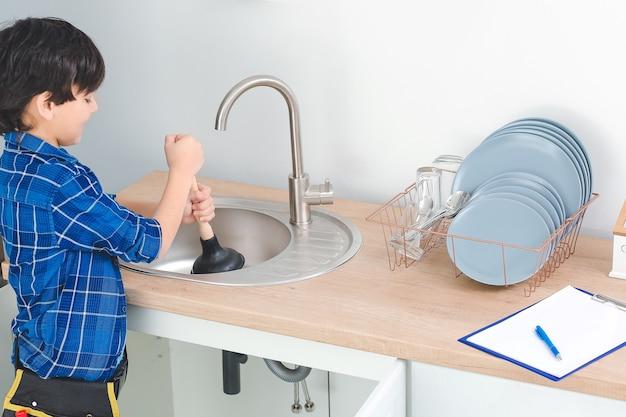 Pequeno encanador consertando pia na cozinha