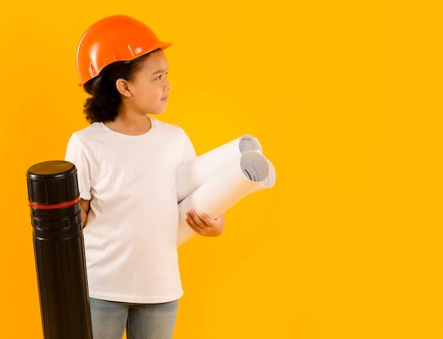 Pequeno engenheiro segurando projetos tiro médio