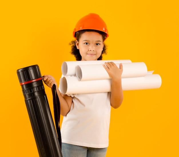 Pequeno engenheiro segurando projetos vista frontal