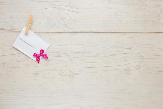 Pequeno envelope com laço pendurado na corda