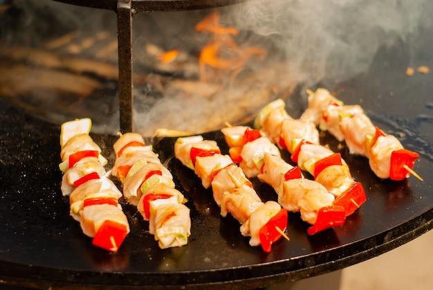 Pequeno espetinho de carne e legumes em espetos de madeira fritos em um braseiro de perto