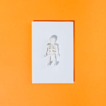 Pequeno esqueleto branco em pedaço de papel