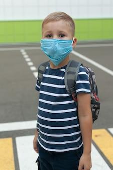 Pequeno estudante com uma máscara durante um surto do vírus corona e da gripe. máscara para prevenção de coronavírus.