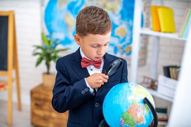 Pequeno estudante olha para o globo com interesse através de lupa