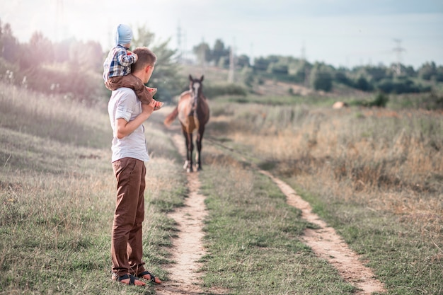 Pequeno filho e seu pai assistindo o cavalo