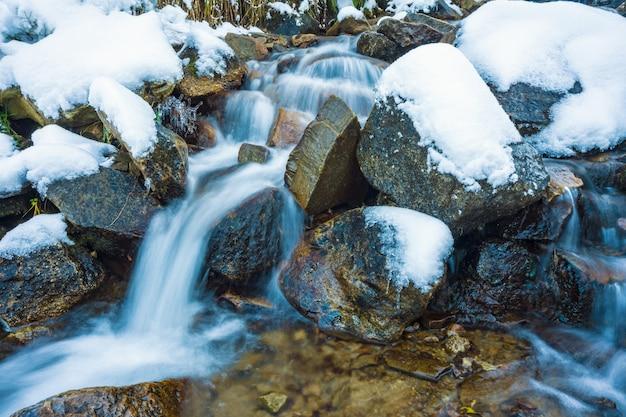 Pequeno fluxo rápido entre pequenas pedras molhadas e neve branca e fria nas pitorescas montanhas dos cárpatos na bela ucrânia e sua natureza fantástica