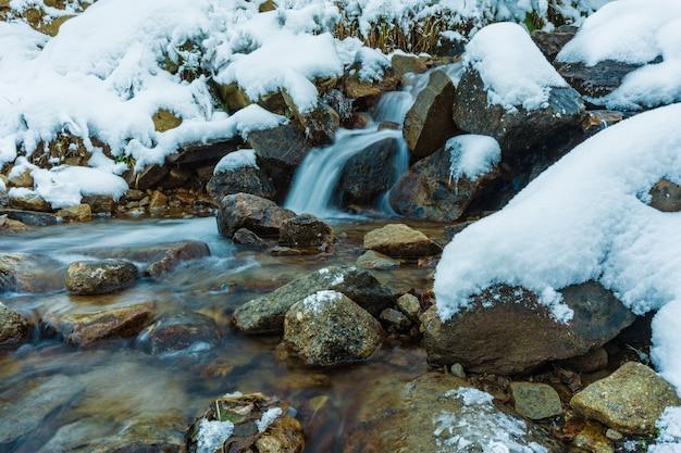 Pequeno fluxo rápido entre pequenas pedras úmidas e neve branca e fria nas pitorescas montanhas dos cárpatos na bela ucrânia e sua natureza fantástica
