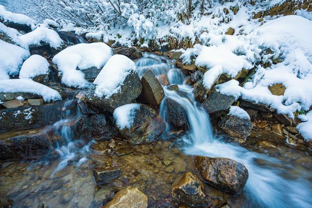 Pequeno fluxo rápido entre pequenas pedras úmidas e neve branca e fria nas pitorescas montanhas dos cárpatos