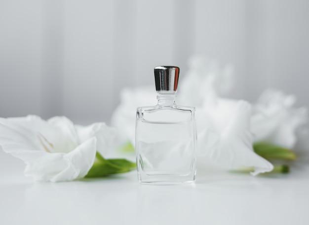Pequeno frasco de perfume com flores sobre branco