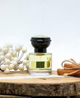 Pequeno frasco de perfume com tampa preta decorado com pau de canela