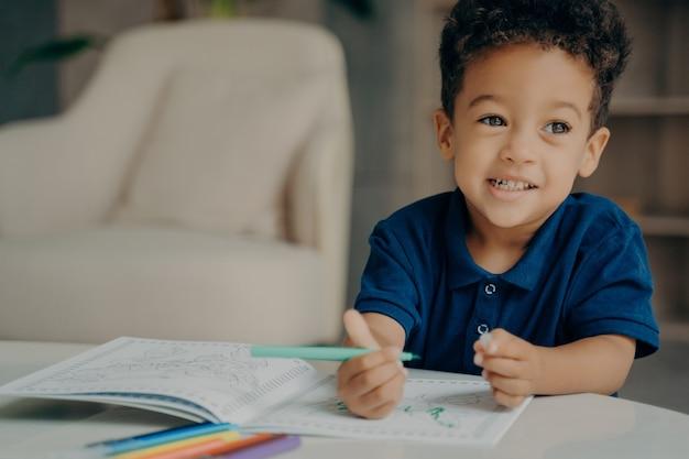 Pequeno garoto afro-americano fofo com camiseta polo azul escuro pintando livro para colorir em casa