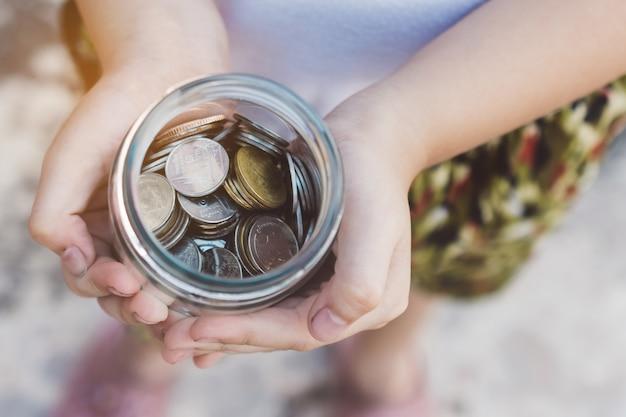 Pequeno garoto mãos segurando moedas