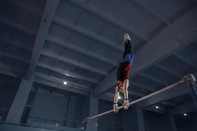 Pequeno ginasta masculino treinando em ginásio flexível e ativo