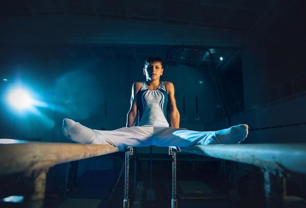 Pequeno ginasta masculino treinando na academia, flexível e ativo