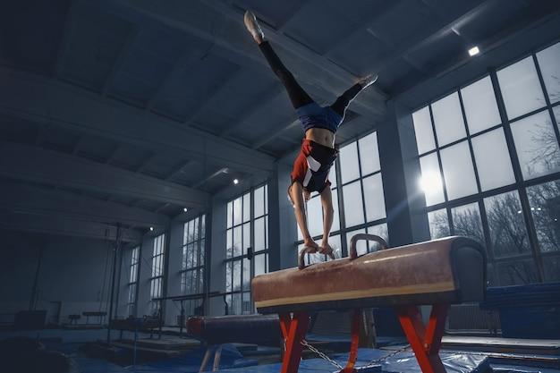 Pequeno ginasta masculino treinando no ginásio, flexível e ativo. caucasiano apto garotinho, atleta em roupas esportivas, praticando em exercícios para força e equilíbrio. movimento, ação, movimento, conceito dinâmico.