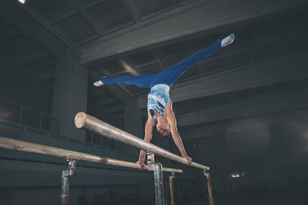 Pequeno ginasta masculino treinando no ginásio, sereno e ativo. caucasiano apto garotinho, atleta em roupas esportivas, praticando em exercícios para força, equilíbrio. movimento, ação, movimento, conceito dinâmico