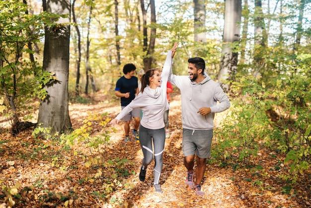Pequeno grupo de amigos felizes correndo na floresta no outono e dando mais cinco.