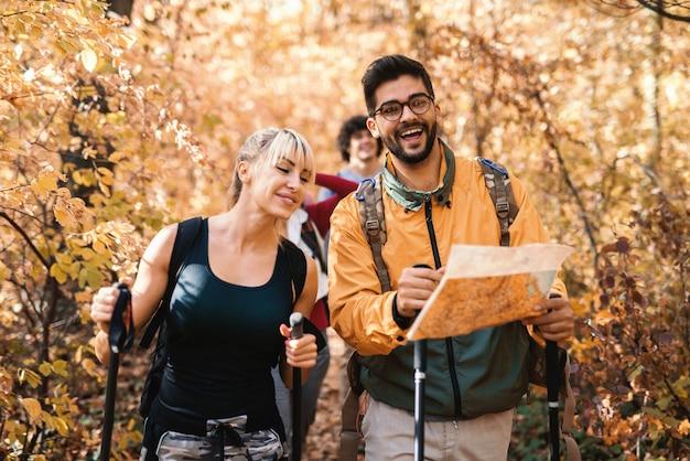 Pequeno grupo de caminhantes que exploram a floresta no outono. em primeiro plano, homem segurando o mapa e a mulher caminhando lado a lado com ele.