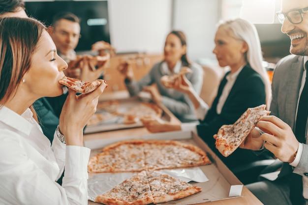 Pequeno grupo de colegas felizes com roupa formal, comendo pizza juntos no almoço.