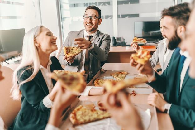 Pequeno grupo de colegas felizes com roupa formal, conversando e comendo pizza juntos no almoço. o talento ganha jogos, mas o trabalho em equipe ganha campeonatos.