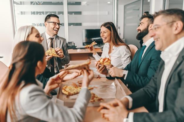Pequeno grupo de colegas felizes com roupa formal, conversando e comendo pizza juntos no almoço.
