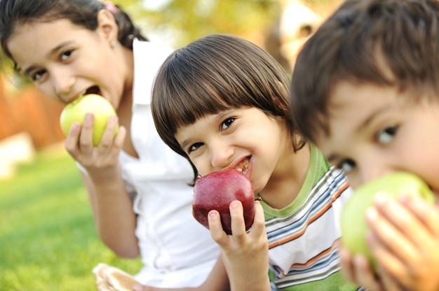 Pequeno grupo de crianças comendo maçãs em conjunto