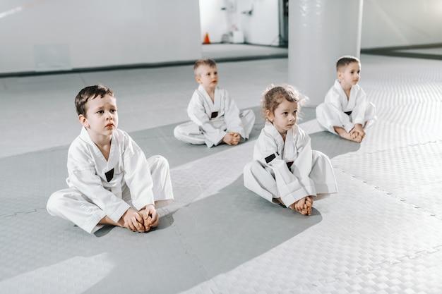 Pequeno grupo de crianças desportivas caucasianas, sentado no chão em taekwondo treinando e ouvindo seu treinador.