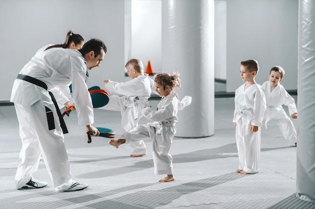 Pequeno grupo de crianças em doboks praticando com seus treinadores movimentos de taekwondo enquanto chutam o alvo do chute.