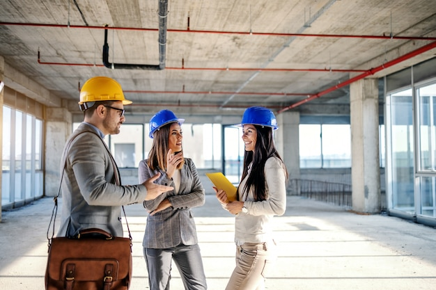 Pequeno grupo de jovens arquitetos altamente motivados e trabalhadores em pé dentro do edifício em processo de construção e conversando sobre novas idéias sobre o objeto relacionado a esse edifício.