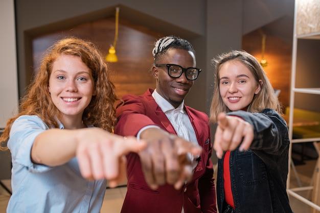 Pequeno grupo de jovens estudantes multiétnicos felizes em trajes casuais apontando para você