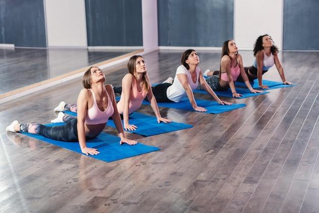 Pequeno grupo de mulheres fazendo pose de ioga cobra na esteira.