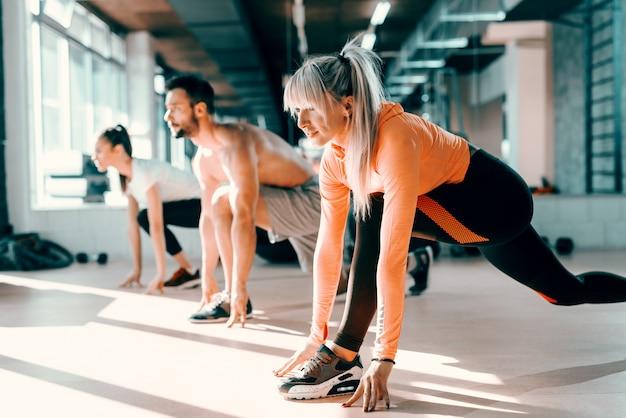 Pequeno grupo de pessoas com hábitos saudáveis, fazendo exercícios de alongamento no chão do ginásio. foco seletivo na mulher loira. no espelho de fundo.