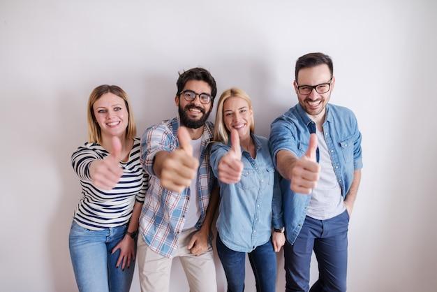 Pequeno grupo de pessoas desistindo polegares em pé contra a parede branca. arranque o conceito do negócio.