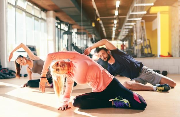 Pequeno grupo de pessoas desportivos no sportswear fazendo alongamento lateral enquanto está sentado no chão do ginásio. no espelho de fundo.