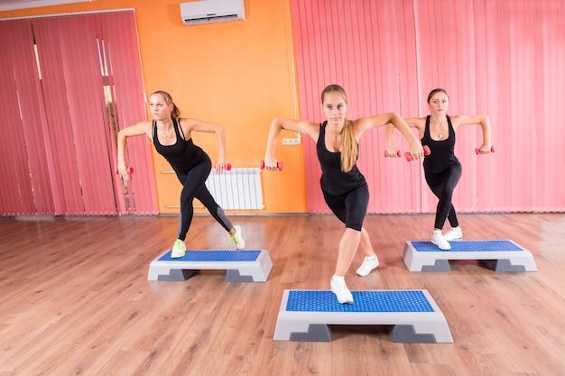 Pequeno grupo de três mulheres na aula de step aeróbico - vista frontal de jovens mulheres segurando pesos nas mãos e fazendo exercícios juntas usando plataformas de step no estúdio de dança