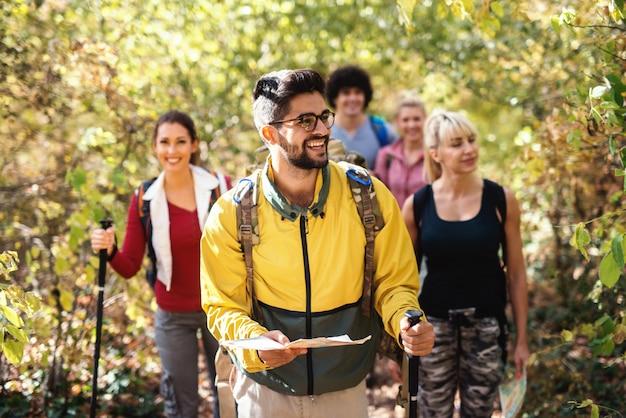 Pequeno grupo feliz de caminhantes que exploram a floresta no outono. foco seletivo no homem liderando o grupo e segurando o mapa.