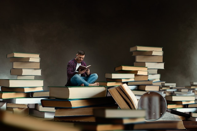 Pequeno homem lendo entre grandes livros e livros didáticos, efeito de escala. obtenção de conhecimento e conceito de educação. aluno estudando o assunto antes do exame