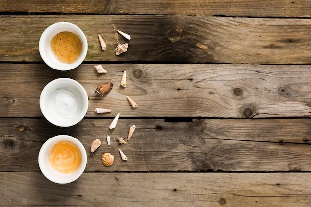Pequeno ingrediente de concha e spa na mesa de madeira enferrujada