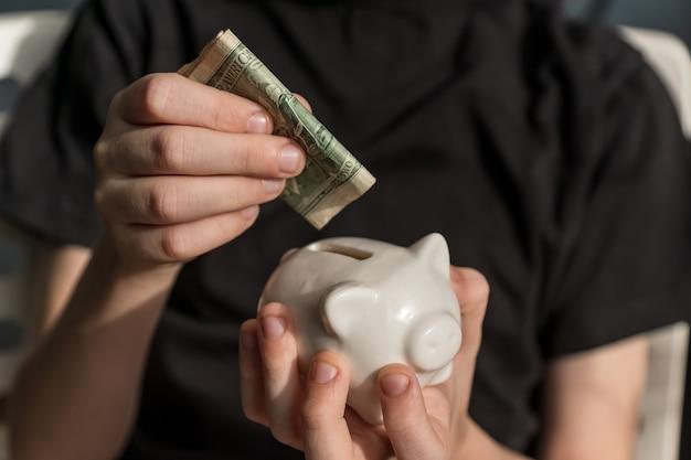 Pequeno investidor colocando seu primeiro dólar americano no cofrinho.