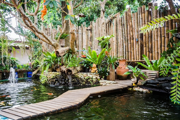 Pequeno jardim com lago de peixes koi e parede de bambu decorado